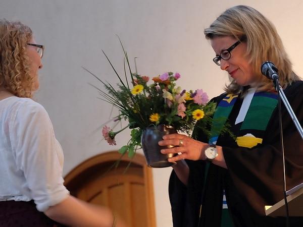 Diemut Meyer überreicht einen Blumenstrauss